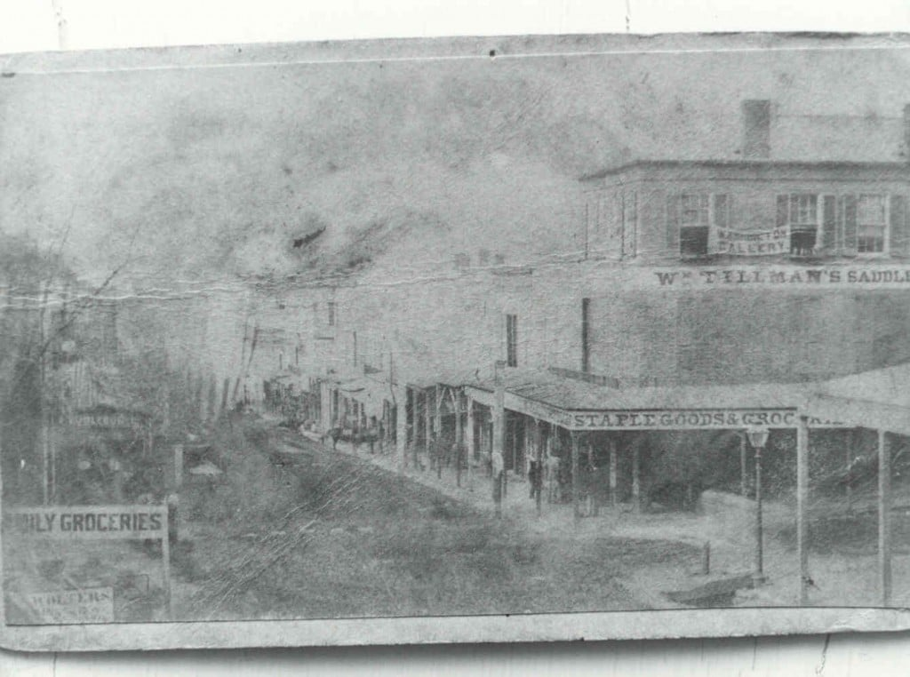 "Corner of Washington & Clay Streets, Circa 1864 Note the Washington Gallery Banner upstairs over William Tillman's Saddle Shop – it was one of many photographic establishments operating in Vicksburg during the Union occupation of the city. Photography was invented by Frenchman Louis Daguerre in 1839, and his invention spread very quickly to America. The earliest documented photographer in Vicksburg was a Mr. Gibbs who owned ""Gibbs Sky-Light Gallery"" on Washington Street in 1849."