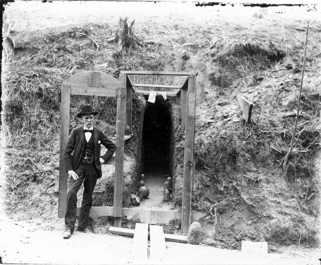 Mr. Tom Lewis standing in front of a cave on Grove Street, Circa 1890's.    To escape the hail of iron being thrown into the city during the siege, citizens dug caves into the sides of the hills for shelter. The caves did their job very well – during the siege less than 20 civilians were killed by the bombardment.    The cave was an excavation in the earth the size of a large room, high enough for the tallest person to stand perfectly erect, provided with comfortable seats, and altogether quite a large and habitable abode (compared with some of the caves in the city) were it not for the dampness and the constant contact with the soft earthy walls.